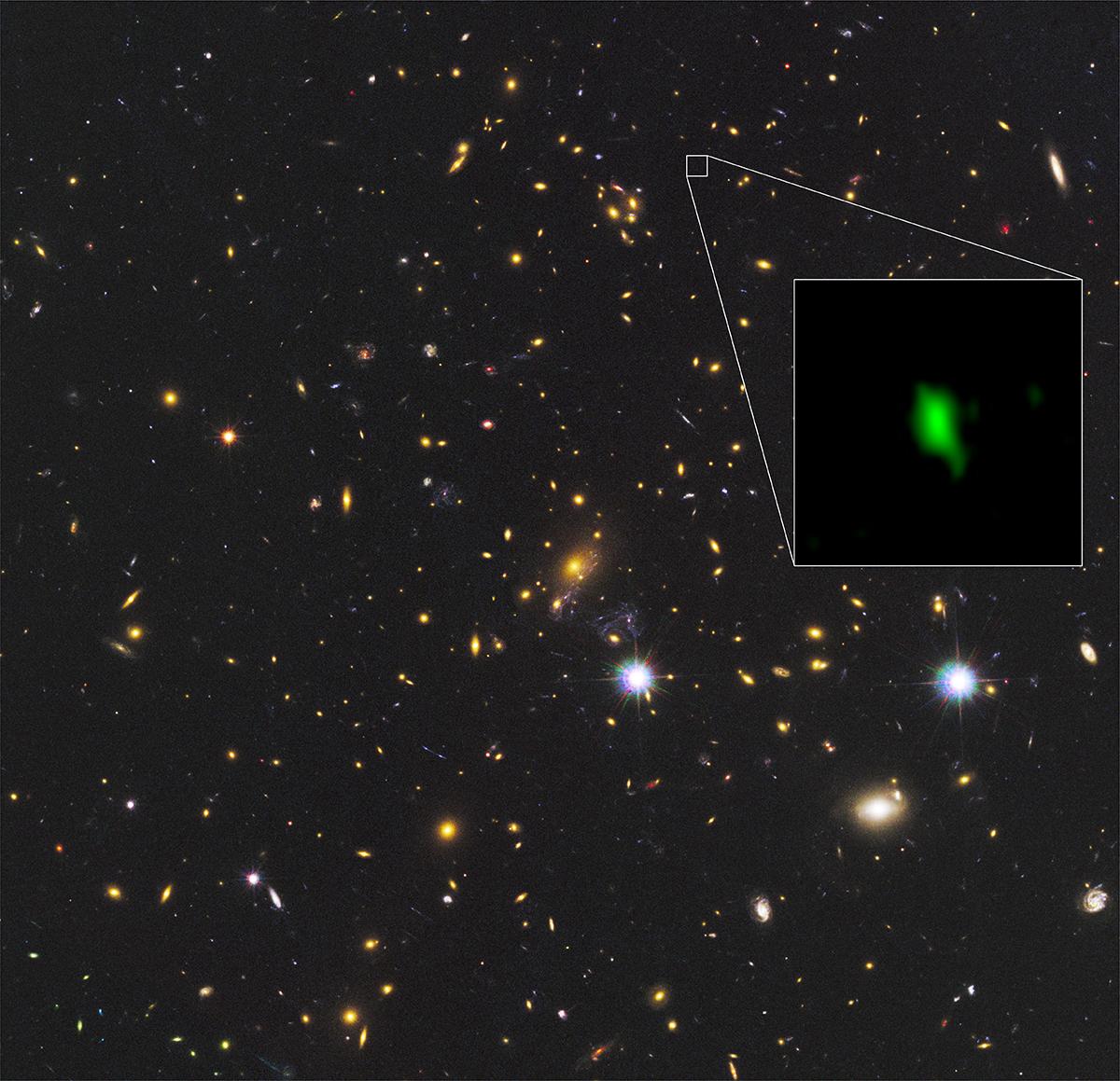 ハッブル宇宙望遠鏡が赤外線で撮影した銀河団MACS J1149.5+2223の画像の一角に、アルマ望遠鏡が電波で観測した銀河MACS1149-JD1を合成した画像。実際にはMACS1149-JD1は銀河団よりもずっと遠い場所にありますが、地球から見ると偶然重なって見えます。画像では、アルマ望遠鏡が観測した酸素の分布を緑色で表現しています。© ALMA (ESO/NAOJ/NRAO), NASA/ESA Hubble Space Telescope, W. Zheng (JHU), M. Postman (STScI), the CLASH Team, Hashimoto et al.