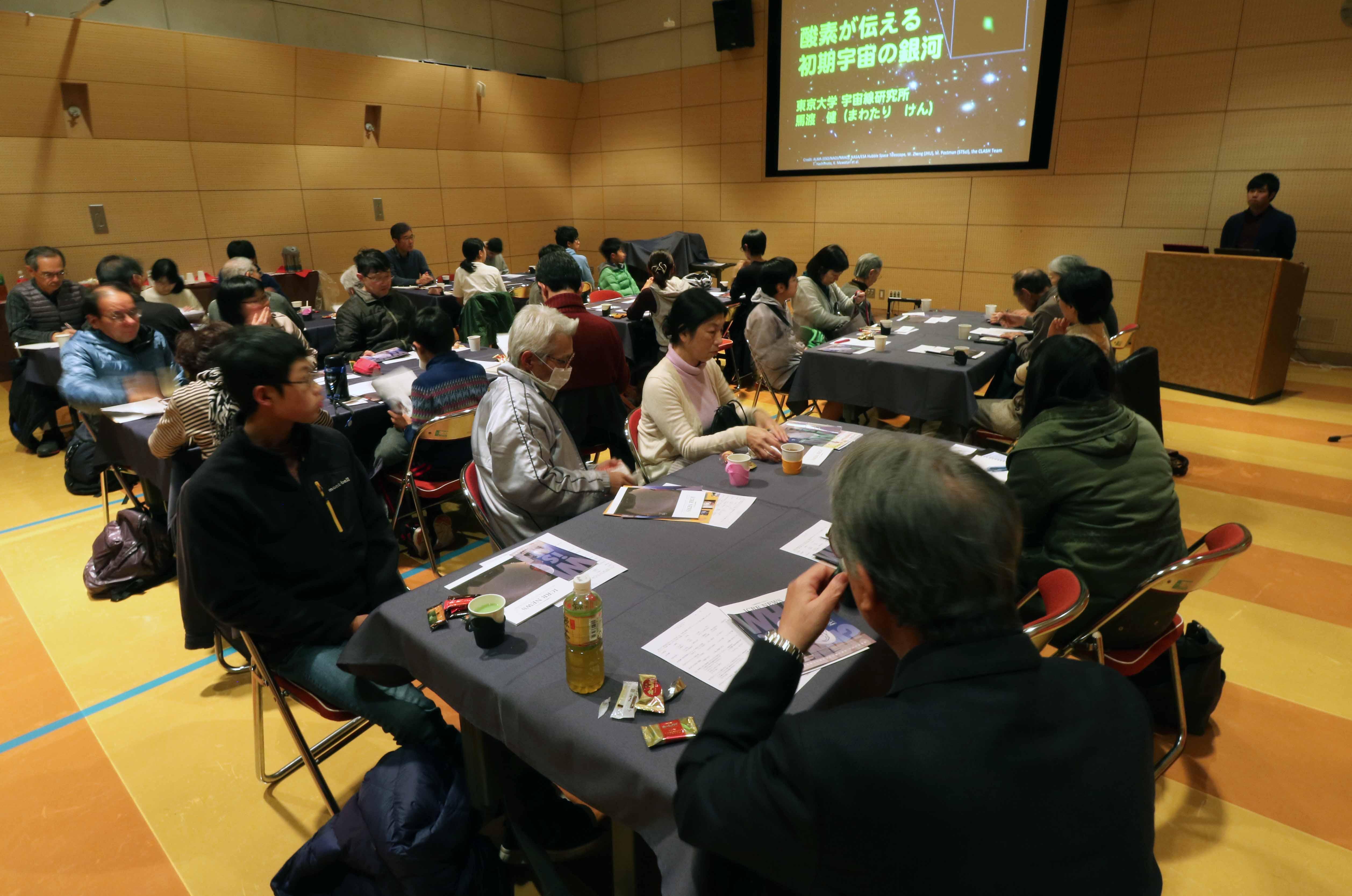 カフェに集まり、熱心に耳を傾ける34人の市民