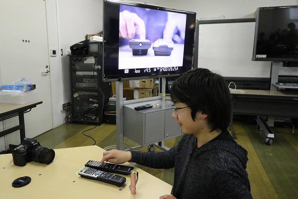 リモコンが発する赤外線をTV画面で確認する小学生