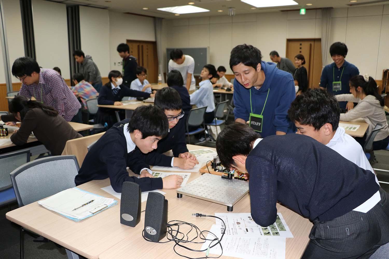 グループで実験用の干渉計を組み立てる高校生ら