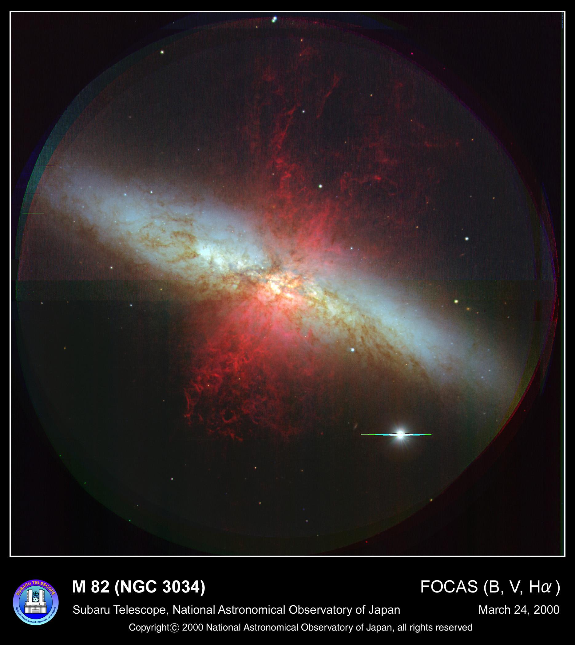 M82銀河の天体写真。銀河中心部から極方向へ電離した水素ガスが噴き出す様子。<br>銀河から吹き出すアウトフローも同じように極方向から吹き出すと考えられています。